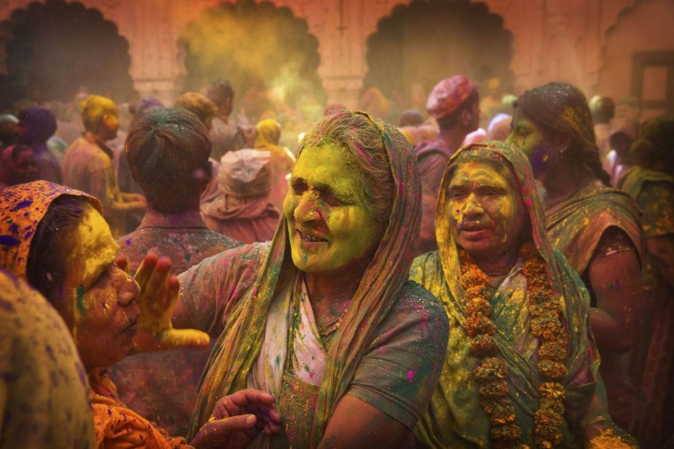 Hindu widows apply colour powder to each other during Holi celebrations at the Gopinath temple, 180 kilometres (112 miles) south-east of New Delhi, India, Monday, March 21, 2016. A few years ago this joyful celebration was forbidden for Hindu widows. Like hundreds of thousands of observant Hindu women they would have been expected to live out their days in quiet worship, dressed only in white, their very presence being considered inauspicious for all religious festivities. (AP Photo/Manish Swarup)