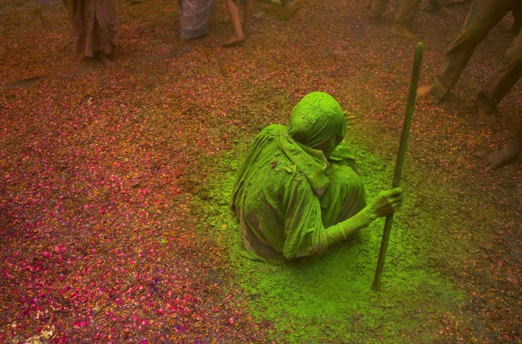 An Indian Hindu widow smeared with colors sits and watches others playing during Holi celebrations at the Gopinath temple, 180 kilometres (112 miles) south-east of New Delhi, India Monday, March 21, 2016. A few years ago this joyful celebration was forbidden for Hindu widows. Like hundreds of thousands of observant Hindu women they would have been expected to live out their days in quiet worship, dressed only in white, their very presence being considered inauspicious for all religious festivities. (AP Photo/Manish Swarup)