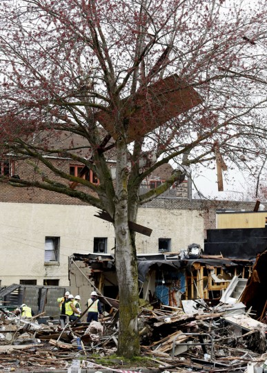 Debris clings to branches in a tree adjacent to the scene of an early morning explosion Wednesday, March 9, 2016, in Seattle. The natural gas explosion sent multiple firefighters to the hospital, none with serious injuries, and reduced several businesses to rubble. (AP Photo/Elaine Thompson)