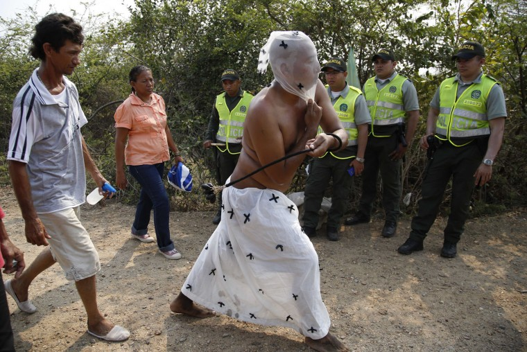 Flagellant Gabriel Puello flogs himself during a Good Friday procession in Santo Tomas, northern Colombia, Friday, March 25, 2016. Puello took part in the procession to ask for the health of his sick father on the day that Christian religious commemorate the crucifixion and death of Jesus Christ. (AP Photo/Fernando Vergara)