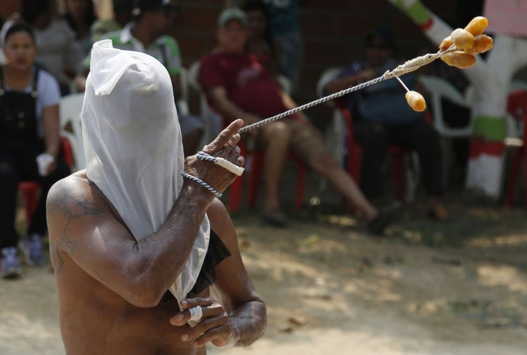 Nicanor Conrrado flogs himself to ask for the health of his sick brother during a Good Friday procession in Santo Tomas, northern Colombia, Friday, March 25, 2016. Dozens of flagellants flog themselves with whips ended in wax balls on the day that Christian religious commemorate the crucifixion and death of Jesus Christ. (AP Photo/Fernando Vergara)