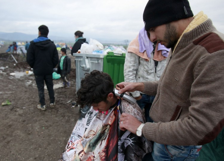 A migrant gives a haircut to another in a makeshift camp at the northern Greek border post of Idomeni, Wednesday, March 16, 2016. Hundreds of migrants and refugees walked out Monday of an overcrowded camp on the Greek-Macedonian border, determined to use a dangerous crossing to head north but were returned to Greece. (AP Photo/Boris Grdanoski)