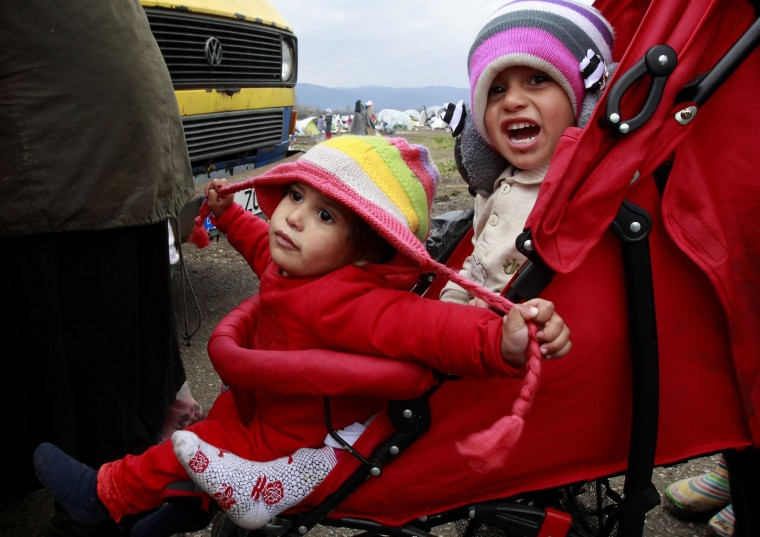 Refugee children sit in a stroller in a makeshift camp at the northern Greek border post of Idomeni, Wednesday, March 16, 2016. Hundreds of migrants and refugees walked out Monday of an overcrowded camp on the Greek-Macedonian border, determined to use a dangerous crossing to head north but were returned to Greece. (AP Photo/Boris Grdanoski)