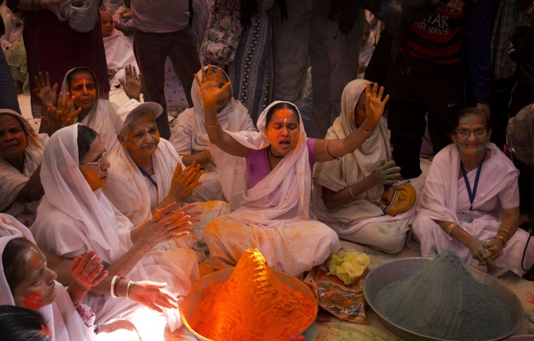 Indian Hindu widows sing and pray before the start of Holi celebrations at the Gopinath temple, 180 kilometres (112 miles) south-east of New Delhi, India, Monday, March 21, 2016. A few years ago this joyful celebration was forbidden for Hindu widows. Like hundreds of thousands of observant Hindu women they would have been expected to live out their days in quiet worship, dressed only in white, their very presence being considered inauspicious for all religious festivities. (AP Photo/Manish Swarup)