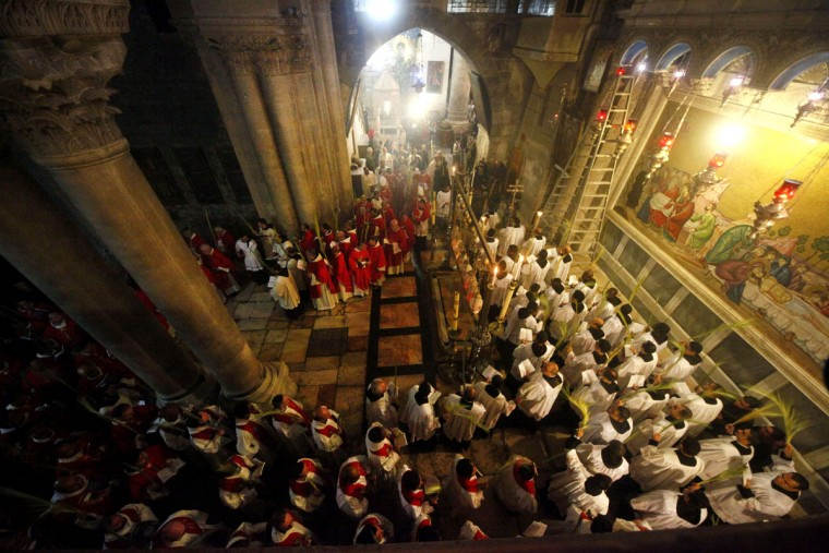 Christian clergymen carry palm fronds during the Palm Sunday procession in the Church of the Holy Sepulcher, traditionally believed by many to be the site of the crucifixion, in Jerusalem's Old City, Sunday, March 20, 2016. (AP Photo/Mahmoud Illean)
