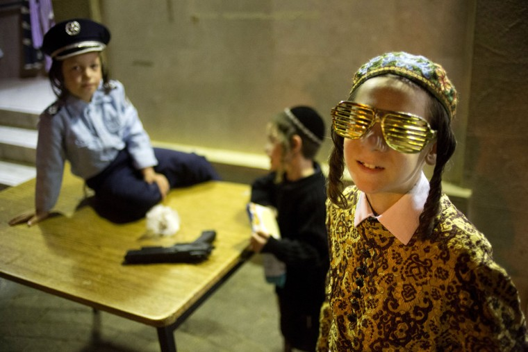 Boys in costume play out side a synagogue of the Tzanz Hasidic dynasty community as others read the Book of Esther, which tells the story of the Jewish festival of Purim, in Netanya, Israel, Wednesday, March 23, 2016. The Jewish holiday of Purim commemorates the Jews' salvation from genocide in ancient Persia, as recounted in the Book of Esther. (AP Photo/Ariel Schalit)