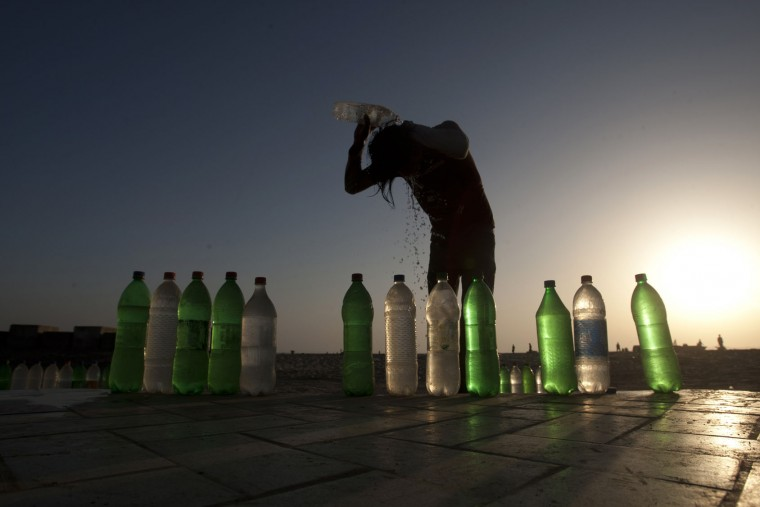 A man pours clean water on him at Clifton beach in Karachi, Pakistan, Tuesday, March 22, 2016. World Water Day is marked on Tuesday, March 22. (AP Photo/Shakil Adil)