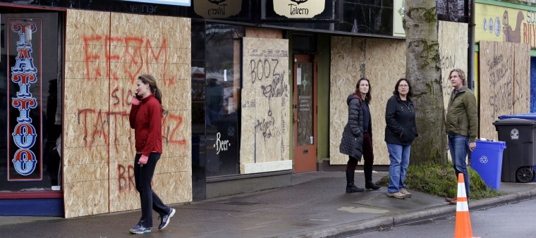 Businesses sport newly boarded-up windows after they were shattered from an early morning explosion about a block away Wednesday, March 9, 2016, in Seattle. The natural gas explosion sent multiple firefighters to the hospital, none with serious injuries, and reduced several businesses to rubble. (AP Photo/Elaine Thompson)