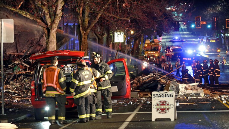 Emergency personnel work at the scene of an early morning explosion Wednesday, March 9, 2016, in Seattle. The natural gas explosion sent multiple firefighters to the hospital, none with serious injuries, and reduced several businesses to rubble. Crews were responding to reports of a natural gas leak when the explosion happened along the main thoroughfare of the city's Greenwood neighborhood, north of downtown, Seattle Fire Department spokeswoman Corey Orvold said. (AP Photo/Elaine Thompson)