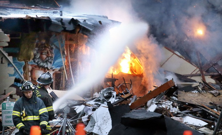 Firefighters pour water on flames burning in the rubble left from an early morning explosion Wednesday, March 9, 2016, in Seattle. The natural gas explosion sent multiple firefighters to the hospital, none with serious injuries, and reduced several businesses to rubble. Crews were responding to reports of a natural gas leak when the explosion happened along the main thoroughfare of the city's Greenwood neighborhood, north of downtown, Seattle Fire Department spokeswoman Corey Orvold said. (AP Photo/Elaine Thompson)