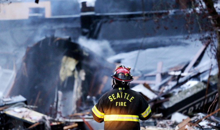 A firefighter looks at the smoldering rubble left from an early morning explosion Wednesday, March 9, 2016, in Seattle. The explosion heavily damaged buildings and injured multiple firefighters. (AP Photo/Elaine Thompson)