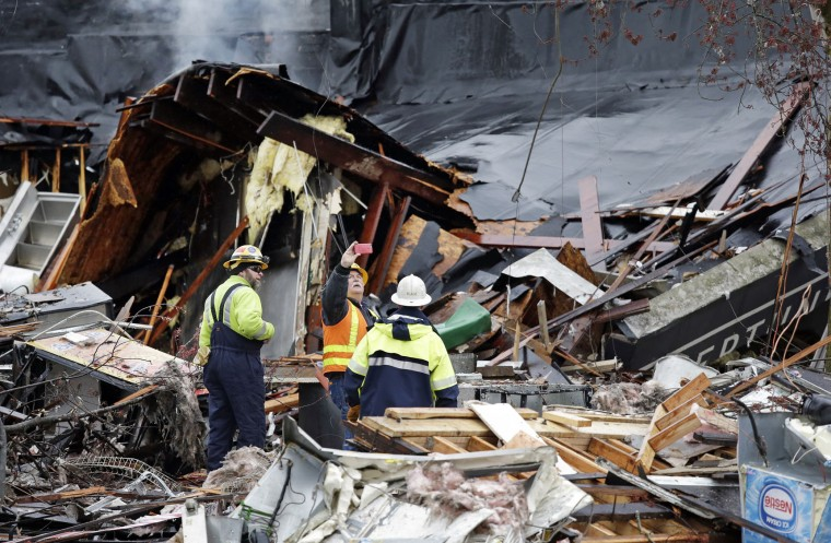 Workers walk in the rubble left from an early morning explosion Wednesday, March 9, 2016, in Seattle. The natural gas explosion sent multiple firefighters to the hospital, none with serious injuries, and reduced several businesses to rubble. Crews were responding to reports of a natural gas leak when the explosion happened along the main thoroughfare of the city's Greenwood neighborhood, north of downtown, Seattle Fire Department spokeswoman Corey Orvold said. (AP Photo/Elaine Thompson)