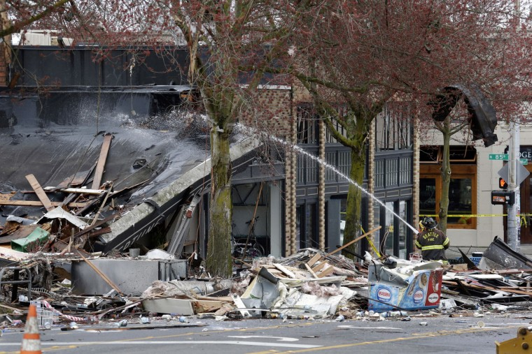 A large piece of debris clings to a tree overhead as a firefighter hoses down a still-smoldering building in the rubble left from an early morning explosion Wednesday, March 9, 2016, in Seattle. The natural gas explosion sent multiple firefighters to the hospital, none with serious injuries, and reduced several businesses to rubble. (AP Photo/Elaine Thompson)