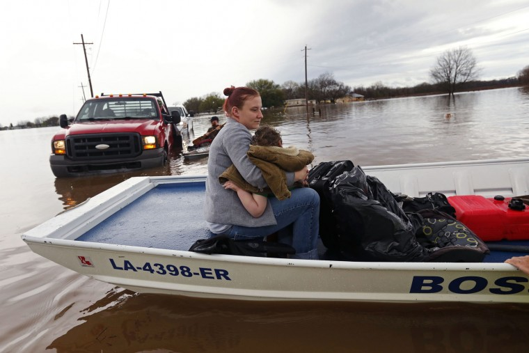 Sarah Yatcko, left, holds her son Tucker Neal as they are evacuated by boat by Bossier County Sheriff personnel during rising floodwaters in Bossier Parish, La., Thursday, March 10, 2016. (AP Photo/Gerald Herbert)