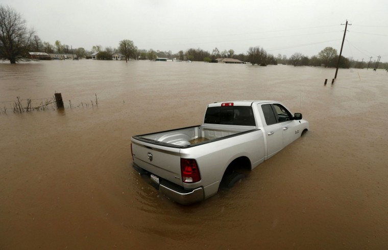 A partially submerged truck sits in rising floodwaters in Bossier Parish, La., Thursday, March 10, 2016. A second round of rain early Thursday hit an already inundated north Louisiana, where flooding in some places was up to the rooftops and in others submerged cars, stranded families and forced evacuations. (AP Photo/Gerald Herbert)
