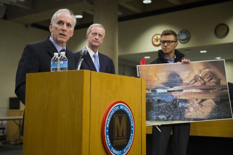 An aide to Metro General Manager Paul Wiedefeld, left, holds up a photo of a track damaged by fire as Wiedefeld speaks during a news conference to announce that the DC Metrorail service will be shut down for a full day, at the Washington Metropolitan Area Transit Authority headquarters, on Tuesday, March 15, 2016, in Washington. At center is DC Council member Jack Evans. (AP Photo/Evan Vucci)
