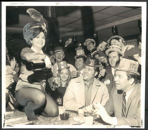 "According to the caption that ran in The Sun with this photo March 18, 1970, ""Susie Cook pours a stiff dram of usquebaugh in Sweeney's bar amid a crowd of St. Patrick's Day revelers smiling with happy Irish eyes."""