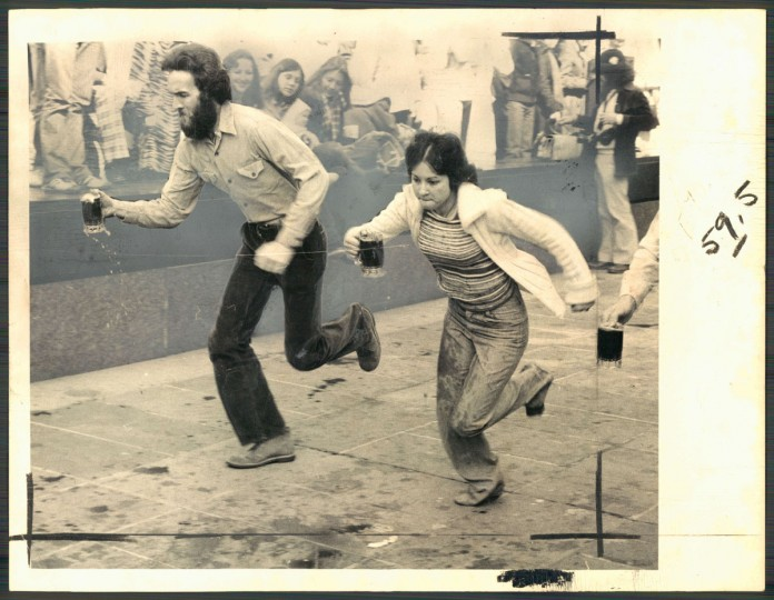 """Bernie Keenan (with beard) defeats Casey Cole in Hopkins Plaza on the way to victory in St. Patrick's Day Beer Mug Race."" March, 1979. (McCardell, The Baltimore Sun)."
