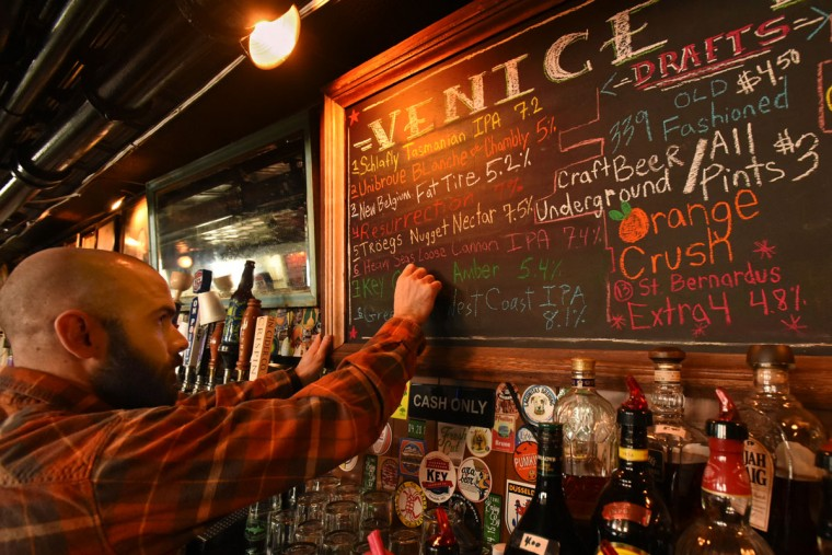 Dominic DeSantis, who purchased the bar from his grandfather, Frank DeSantis Jr., changes the craft beer offerings on the blackboard. (Amy Davis/Baltimore Sun)