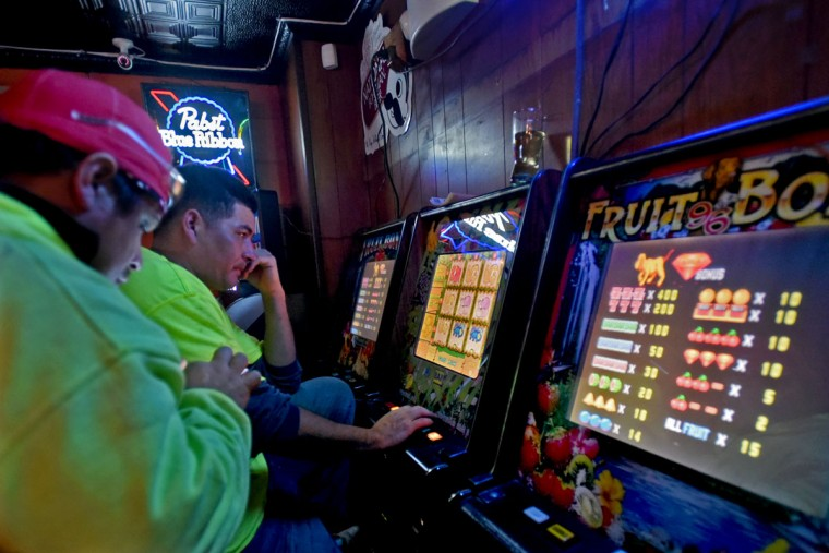 Walter Romero, left, chats with Carlos Cardona, who plays the slots and RaceTrax every day. The clientele at the Venice Tavern reflects the diversity of Highlandtown today. (Amy Davis/Baltimore Sun)