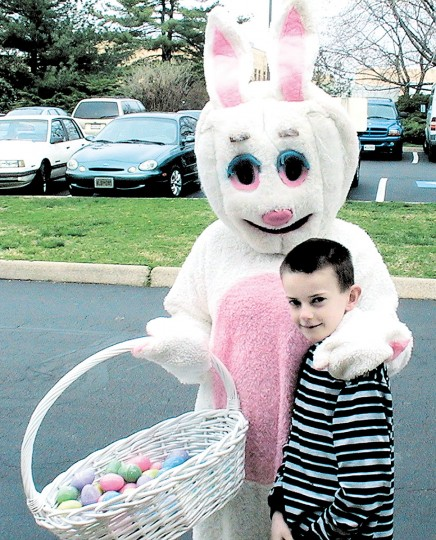 Connor Livingston of Davidsonville takes a break from egg hunting to pose with Easter Bunny. (Lea Hurt/Baltimore Sun Media Group)