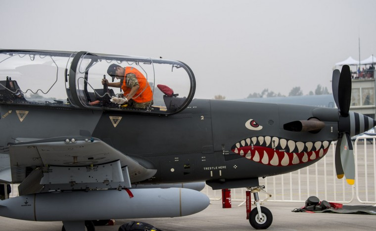 A Peruvian ground crew member cleans a Korean-made Peruvian KAI KT-1 aircraft exhibited at the international airport during the XIX Air and Space Fair (FIDAE) in Santiago on March 28, 2016. (MARTIN BERNETTI/AFP/Getty Images)