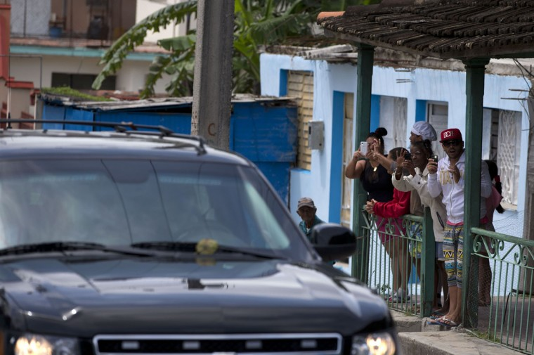 Local residents shoot cell phone video from their front porch as the convoy carrying U.S. First Lady Michelle Obama arrives at Hemmingway House, in the San Francisco de Paula district of Havana, Cuba, Monday, March 21, 2016. (AP Photo/Rebecca Blackwell)