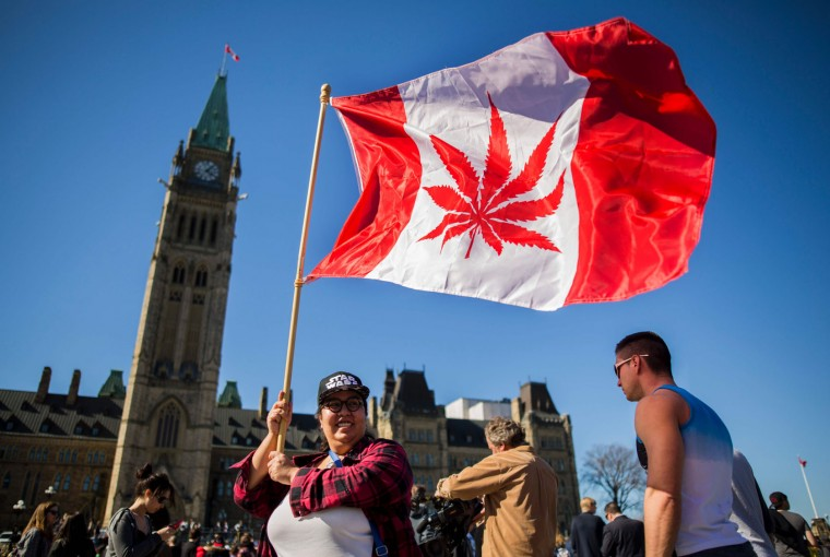 A woman waves a flag with a marijuana leaf on it next to a group gathered to celebrate National Marijuana Day on Parliament Hill in Ottawa, Canada on April 20, 2016. Canada will take steps next year to legalize marijuana, Health Minister Jane Philpott announced. Philpott offered several reasons for ending the ban on pot, including the view that laws in Canada and abroad criminalizing marijuana use have been both overly-harsh and ineffective. (Chris Roussakis/AFP/Getty Images)