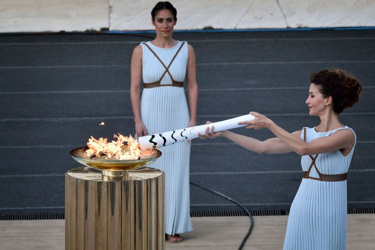 Actress Katerina Lechou (R) performing as the high priestess lights the Olympic flame, during the handover ceremony at the Panathinean stadium in Athens, on April 27, 2016. Greece on April 27 handed over to Brazilian officials the Olympic flame of the Rio Games as the 100-day countdown to the August 5 opening ceremony begins. (AFP Photo/Louisa Gouliamaki)