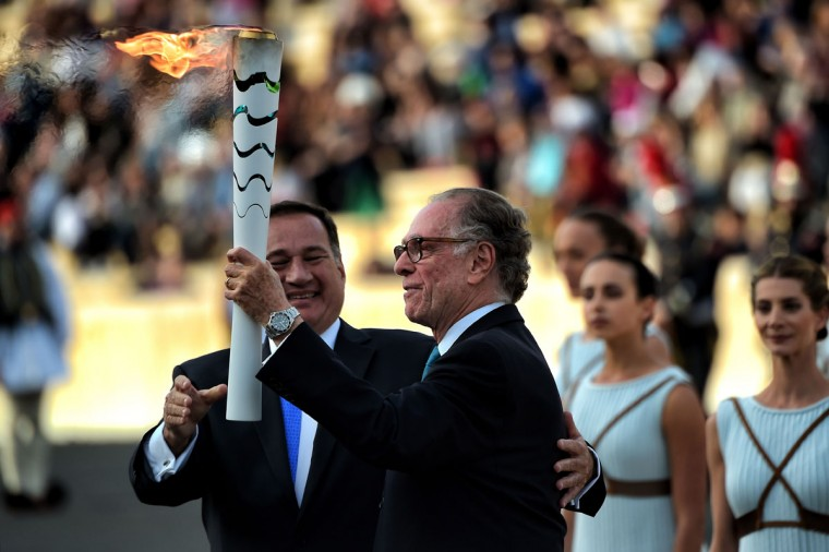 President of the Hellenic Olympic Committee Spyros Kapralos (L) passes the Olympic flame to Rio 2016 Organising Committee President Carlos Nuzman (R) during the handover ceremony at the Panathinean stadium in Athens, on April 27, 2016. Greece on April 27 handed over to Brazilian officials the Olympic flame of the Rio Games as the 100-day countdown to the August 5 opening ceremony begins. (AFP Photo/Aris Messinis)