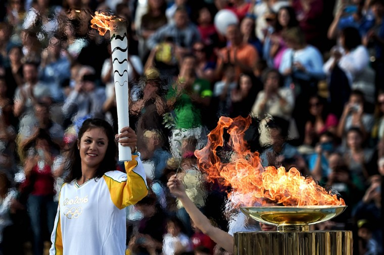 The torchbearer, Greek Rowing World Champion Katerina Nikolaidou, holds the Olympic flame, during the handover ceremony at the Panathinean stadium in Athens, on April 27, 2016. Greece on April 27 handed over to Brazilian officials the Olympic flame of the Rio Games as the 100-day countdown to the August 5 opening ceremony begins. (AFP Photo/Aris Messinis)