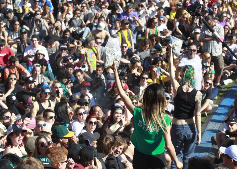 4/20 staff hand out free joints as thousands of people gathered at 4/20 celebrations on April 20, 2016 at Sunset Beach in Vancouver, Canada. The Vancouver 4/20 event is the largest free protest festival in the city, with day-long music, public speakers and the world's only open-air public cannabis farmer's market where people sell all kinds of cannabis and extracts while educating the crowd about medical marijuana, political involvement and activism. Canadian Federal Health Minister Jane Philpott says Canada will roll out the legislation in the spring of 2017 to begin the process of legalizing and regulating marijuana. (Photo by Jeff Vinnick/Getty Images)