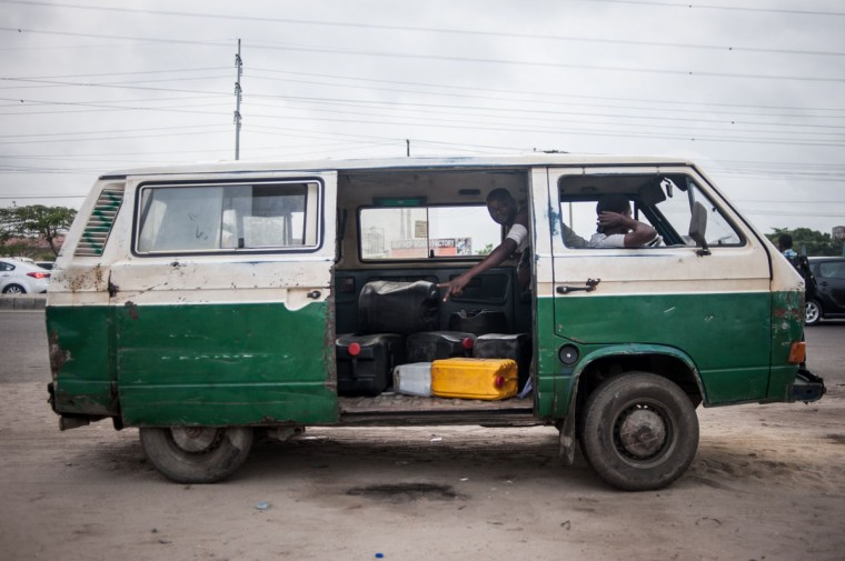 A mini bus with containers filled with fuel stands on the side of the road selling petrol on the black market in Lagos on April 6, 2016. Fuel dependant Nigeria has been in the grip of fuel scarcity for the last couple of weeks affecting peoples ability to generate electricity. Due to the fuel scarcity, there has been an increase in the price of goods, commodities and transport fares as well as an increased activity of black market fuel hawkers that sell diluted fuel at extortionate prices. (AFP Photo/Stefan Heunis)