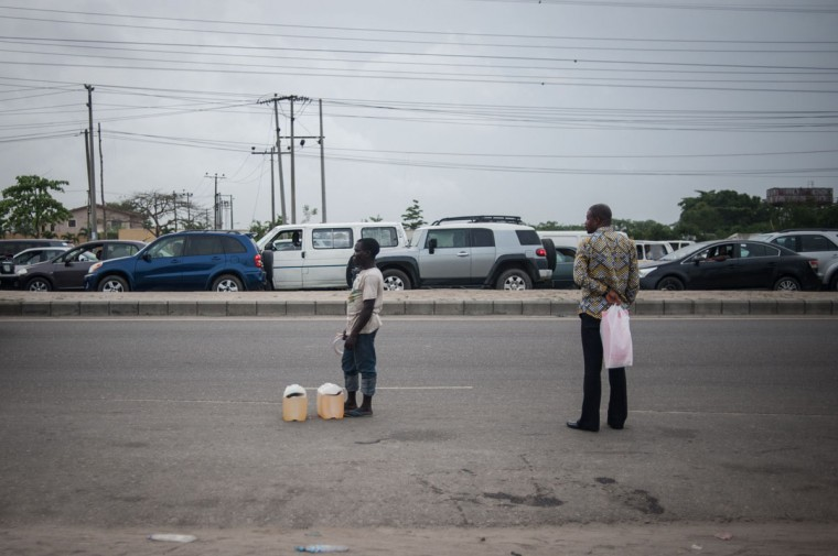 A black market fuel hawker stands next to the road waiting for a customer in Lagos on April 6, 2016.Fuel dependant Nigeria has been in the grip of fuel scarcity for the last couple of weeks affecting peoples ability to generate electricity. Due to the fuel scarcity, there has been an increase in the price of goods, commodities and transport fares as well as an increased activity of black market fuel hawkers that sell diluted fuel at extortionate prices. (AFP Photo/Stefan Heunis)