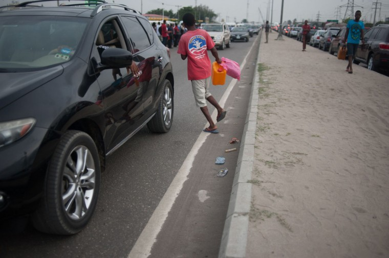 A black market fuel hawker runs across the road carrying a container filled with fuel in Lagos on April 6, 2016. Fuel dependant Nigeria has been in the grip of fuel scarcity for the last couple of weeks affecting peoples ability to generate electricity. Due to the fuel scarcity, there has been an increase in the price of goods, commodities and transport fares as well as an increased activity of black market fuel hawkers that sell diluted fuel at extortionate prices. (AFP Photo/Stefan Heunis)