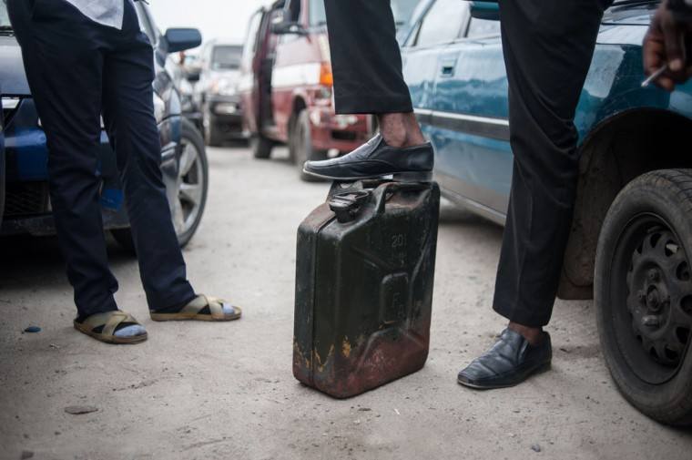A man stands with his foot on top of his jerrican waiting to buy some fuel in Lagos on April 6, 2016. Fuel dependant Nigeria has been in the grip of fuel scarcity for the last couple of weeks affecting peoples ability to generate electricity. Due to the fuel scarcity, there has been an increase in the price of goods, commodities and transport fares as well as an increased activity of black market fuel hawkers that sell diluted fuel at extortionate prices. (AFP Photo/Stefan Heunis)
