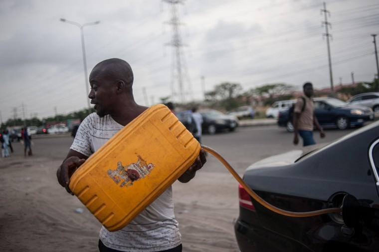 A black market fuel hawker fills the car with fuel on the side of the road in Lagos on April 6, 2016. Fuel dependant Nigeria has been in the grip of fuel scarcity for the last couple of weeks affecting peoples ability to generate electricity. Due to the fuel scarcity, there has been an increase in the price of goods, commodities and transport fares as well as an increased activity of black market fuel hawkers that sell diluted fuel at extortionate prices. (AFP Photo/Stefan Heunis)