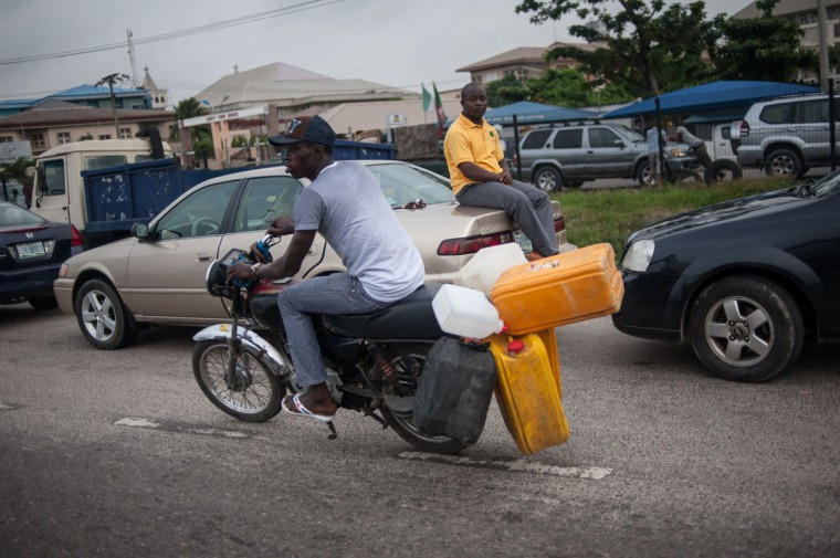 A motorcyclist carries empty fuel containers on his motorcycle as he heads to the fuel station Lagos on April 6, 2016. Fuel dependant Nigeria has been in the grip of fuel scarcity for the last couple of weeks affecting peoples ability to generate electricity. Due to the fuel scarcity, there has been an increase in the price of goods, commodities and transport fares as well as an increased activity of black market fuel hawkers that sell diluted fuel at extortionate prices. (AFP Photo/Stefan Heunis)