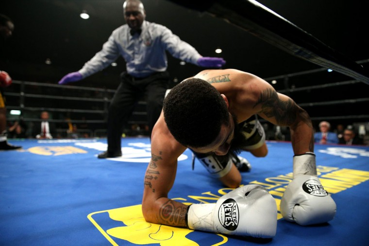 WASHINGTON, DC - APRIL 01: Gerald Tucker falls to the mat as he fights Antoney Napunyi exchange punches in their super featherweights bout at the DC Armory on April 1, 2016 in Washington, DC. (Photo by Patrick Smith/Getty Images)