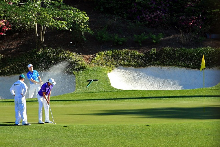 Jordan Spieth of the United States plays a shot from a bunker on the 12th hole as Smylie Kaufman of the United States and caddie Aaron Alpern look on during the final round of the 2016 Masters Tournament at Augusta National Golf Club on April 10, 2016 in Augusta, Georgia. (Photo by David Cannon/Getty Images)