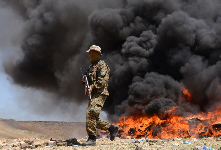 An Afghan security officer walks past a pile of confiscated drugs being burned in ceremony in Jalalabad, east of Kabul, Afghanistan, Tuesday, April 12, 2016 Around 21 tons of opium, heroin, alcohol and hashish were set on fire, officials said. (AP Photo/Mohammad Anwar Danishyar)