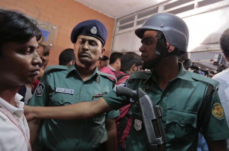 Bangladeshi policemen try to control the crowd of onlookers at a building where two people were found stabbed to death in Dhaka, Bangladesh, Monday, April 25, 2016. Police in Bangladesh say unidentified assailants have stabbed two men to death, including a gay rights activist who also worked for the U.S. Agency for International Development. (AP Photo/A.M.Ahad)