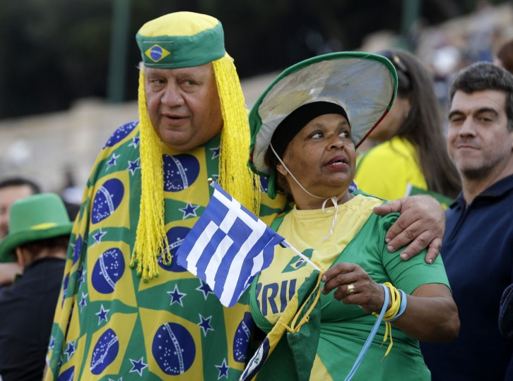 Brazilians attend the handover ceremony for the Olympic Flame at Panathinean stadium in Athens, Wednesday, April 27, 2016. The Olympic flame was handed to organizers of the Rio de Janeiro Games on Wednesday, 100 days before the opening ceremony. (AP Photo/Thanassis Stavrakis)