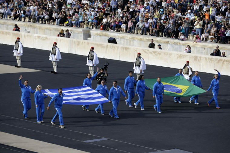 Greek Olympic Champions carry the flags of Greece, left, and Brazil as they arrive for the handover ceremony for the Olympic Flame at Panathinean stadium in Athens, Wednesday, April 27, 2016. The flame arrives in Brazil on May 3, and will be relayed across the vast country by about 12,000 torchbearers before the Aug. 5 opening ceremony in Rio de Janeiro's Maracana Stadium. (AP Photo/Thanassis Stavrakis)