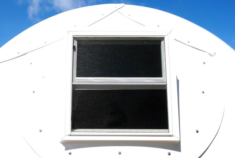 In this Friday, April 22, 2016 photo, the window of a dome-shaped shelter is shown at the First Assembly of God church in Honolulu. The church is looking into an unexpected solution to state's homeless crisis: they're planning to erect Alaska-made igloos to house homeless families. The snow-inspired dome-shape structures would appear at first glance to be a misfit among the island state's palm trees and sandy beaches, but their bright fiberglass exterior reflects the sun, shading those inside. (AP Photo/Caleb Jones)