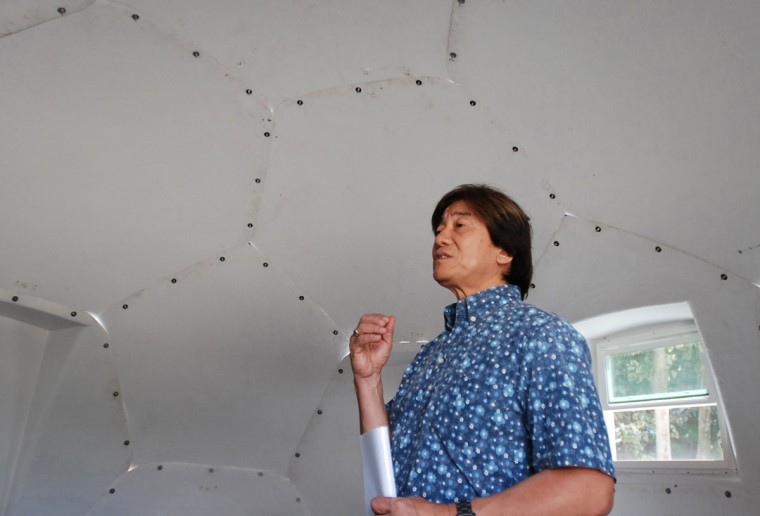 In this Friday, April 22, 2016 photo, Daniel Kaneshiro, a pastor at First Assembly of God church, talks to The Associated Press inside a dome-shaped shelter at the church in Honolulu. The church is looking into an unexpected solution to state's homeless crisis: they're planning to erect Alaska-made igloos to house homeless families. The snow-inspired dome-shape structures would appear at first glance to be a misfit among the island state's palm trees and sandy beaches, but their bright fiberglass exterior reflects the sun, shading those inside. (AP Photo/Caleb Jones)