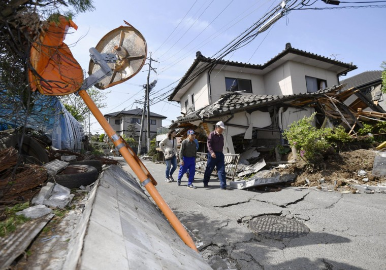 Residents walk past a house damaged by a magnitude-6.5 earthquake in Mashiki, Kumamoto prefecture, southern Japan, Friday, April 15, 2016. The powerful earthquake struck Thursday night, knocking down houses and buckling roads. (Yu Nakajima/Kyodo News via AP)