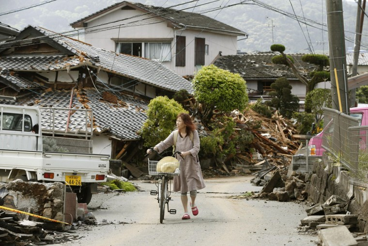 A woman pushes a bicycle through an earthquake-damaged residential area in Mashiki, Kumamoto prefecture, Japan Sunday, April 17, 2016. After two nights of earthquakes, flattened houses and triggered major landslides in southern Japan, 91,000 people had evacuated from their homes, according to a Kumamoto prefectural official. (Shohei Miyano/Kyodo News via AP)