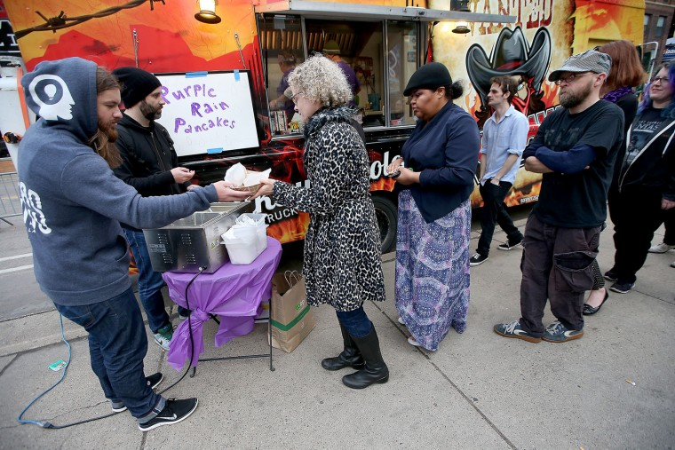 "Harry Awe, left, and Josh Combs, hand out free ""Purple Rain Pancakes,"" outside of First Avenue as fans honoring Prince leave the area, Friday, April 22, 2016 in Minneapolis. Prince, widely acclaimed as one of the most inventive and influential musicians of his era with hits including ""Little Red Corvette,"" ''Let's Go Crazy"" and ""When Doves Cry,"" was found dead at his home on Thursday in suburban Minneapolis, according to his publicist. He was 57. (Elizabeth Flores/Star Tribune via AP)"