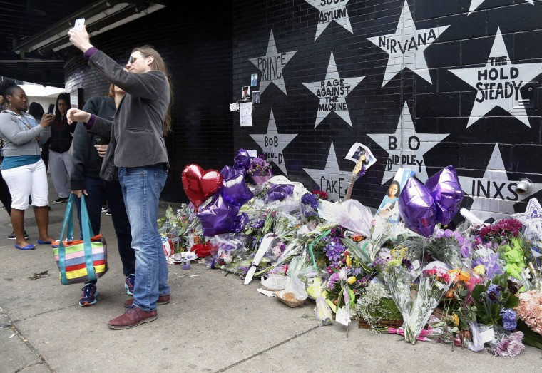 Fans pose for photos and selfies at the Prince star and memorial at First Avenue Friday, April 22, 2016 in Minneapolis where he often performed. The pop super star died Thursday at the age of 57. (AP Photo/Jim Mone)